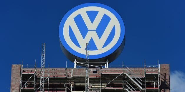 A worker stands on a scaffold lift, under a giant VolksWagen logo at VolksWagen's original headquarters...