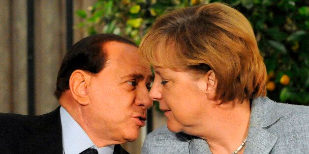 Italy's Prime Minister Silvio Berlusconi (L) speaks to German Chancellor Angela Merkel during a joint...