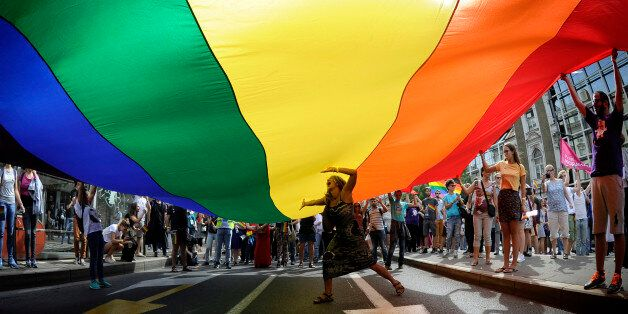 A woman dances under a huge rainbow flag during the Gay Pride parade in Belgrade on September 18, 2016....