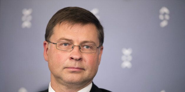 Valdis Dombrovskis, vice president of the European Commission, listens during a press conference following...