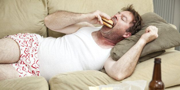Unemployed middle aged man at home on the couch in his underwear, eating a hamburger, with a marijuana...