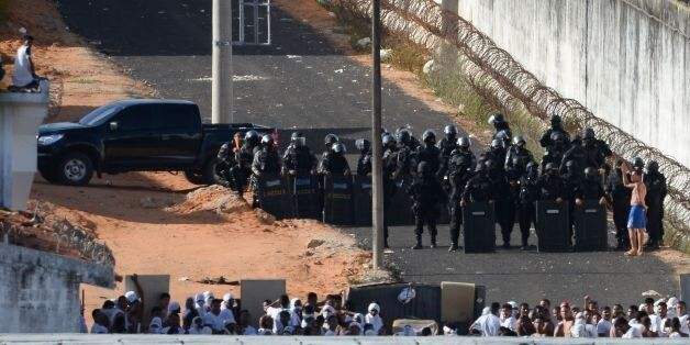 Riot police agents group and approach to negociate with an inmate's delegate (R) during a rebellion at...