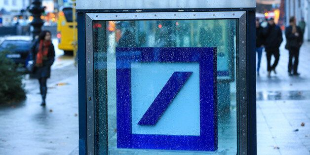 A Deutsche Bank AG logo sits inside a glass display case outside a bank branch in Berlin, Germany, on...