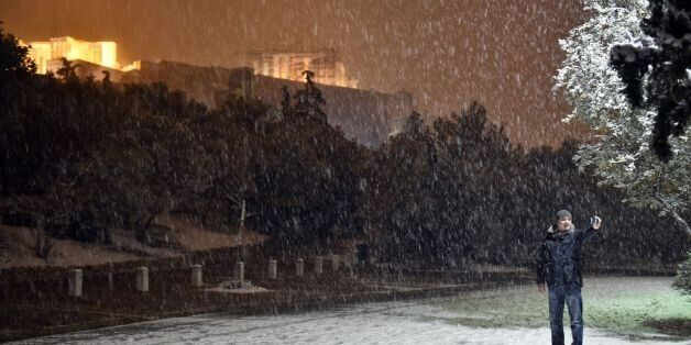 A man takes a selfie with the Acropolis in the background during heavy snowfall in central Athens on...