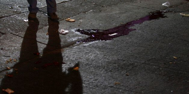 The shadow of a police officer is cast near a puddle of blood at a crime scene outside a nightclub in...