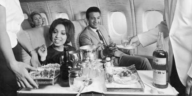 circa 1965: Flight crew serving food and beverages to passengers aboard an airplane, 1960s. (Photo by...