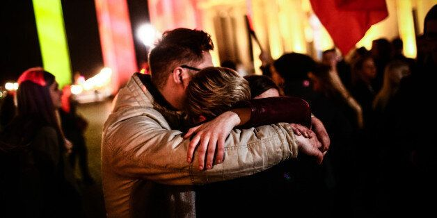 BERLIN, March 22, 2016 -- People hug each other as they gather in front of the Brandenburg Gate to mourn...