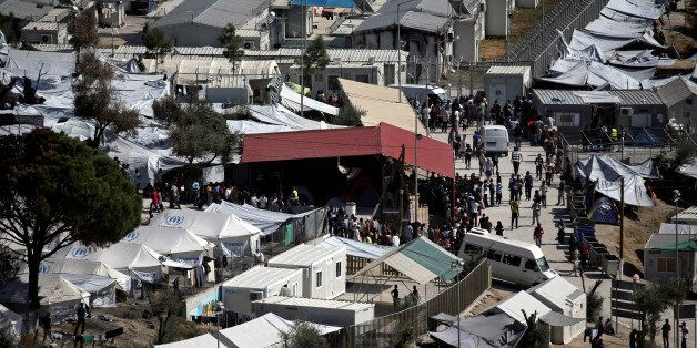 Refugees and migrants line up for food distribution at the Moria migrant camp on the island of Lesbos,...
