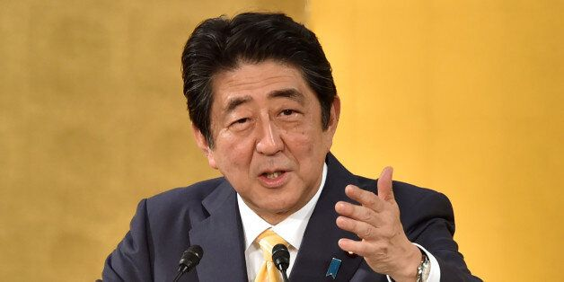 Japan's Prime Minister Shinzo Abe delivers a speech at an annual new year party hosted by three business...