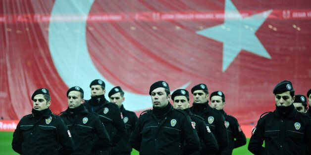 Turkish riot police stand guard before a soccer exhibition game at Besiktas Vodafone Arena in Istanbul,...