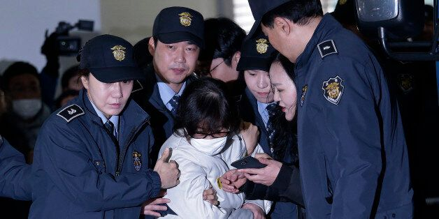 Choi Soon-sil (C), the jailed confidante of South Korean President Park Geun-hye, arrives for questioning...
