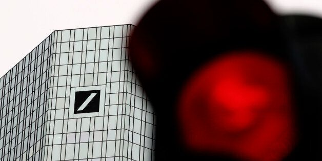 A red traffic light is pictured in front of the Deutsche Bank headquarters in Frankfurt, Germany, September...