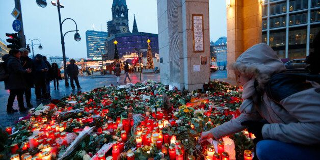 Flowers and candles are placed near the Christmas market at Breitscheid square in Berlin, Germany, December...