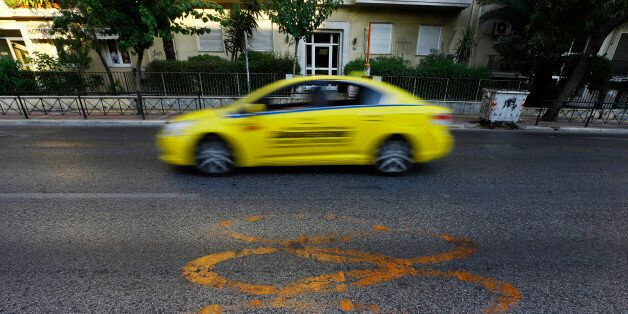 A taxi drives by fading Olympic rings which mark the Olympic Traffic Lane on an avenue leading to the...