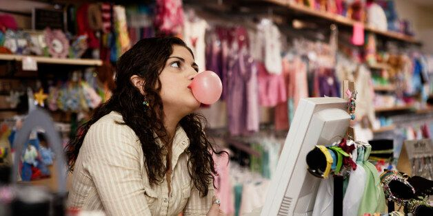 Young woman behind store counter, blowing