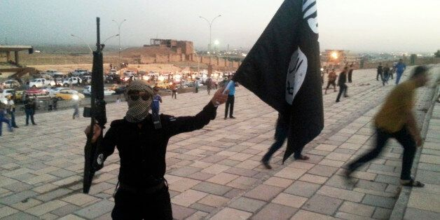 A fighter of the Islamic State of Iraq and the Levant (ISIL) holds an ISIL flag and a weapon on a street...