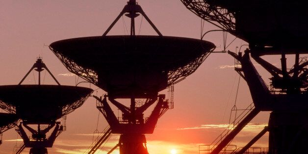 Sunset silhouetting three of the 27 dish antennas the make up the Very Large Array. The VLA is the world's...