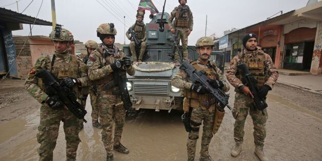 Iraqi pro-government forces patrol the eastern part of the embattled Iraqi city of Mosul on December...