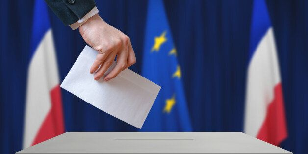 Election in France. Voter holds envelope in hand above vote ballot. French and European Union flags in