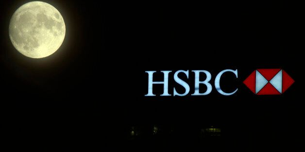 The moon rises over the HSBC building in the Canary Wharf financial district of London, a day before