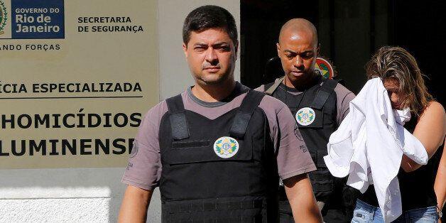 Francoise Souza Oliveira, 40, wife of Greek Ambassador for Brazil Kyriakos Amiridis, is escorted by police...