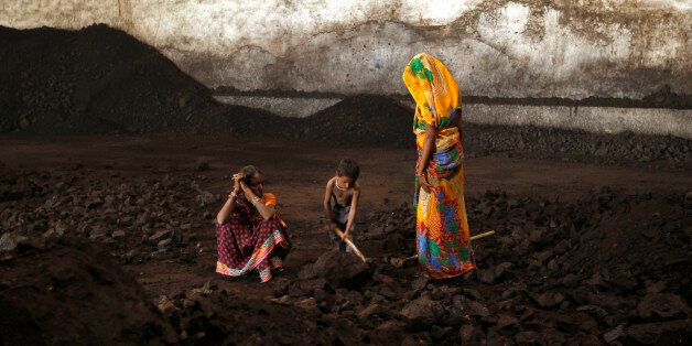 Labourers rest as a boy playfully shovels coal at a yard in the western Indian city of Ahmedabad November...