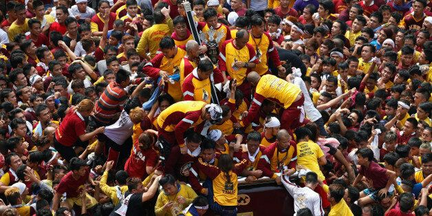 Devotees jostle to touch the image of Black Nazarene as they parade a black statue of Jesus Christ during...
