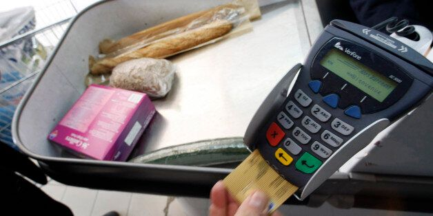 A shopper pays with his credit card in a supermarket in Nice southern France, February 25, 2008 as the...