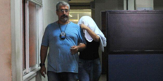 A Brazilian civil policeman escorts the wife of Greece's ambassador to Brazil Kyriakos Amiridis, Francoise...