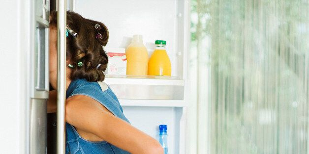 Profile of a young woman 25 years old having curlers in hair, wearing high heels and blue short dress,...
