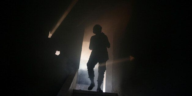 A Civil Defence member walks through smoke as he tries to put out a fire inside a building after shelling...