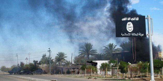 Smoke raises behind an Islamic State flag after Iraqi security forces and Shiite fighters took control...