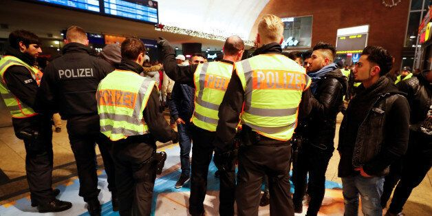 Police officers of Germany's federal police Bundespolizei check young men at the main railways station...