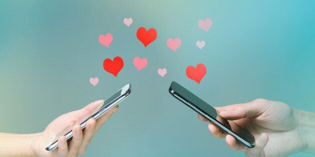 Young man and woman's hands holding smart phones with hearts floating over