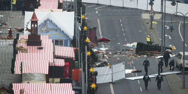 Barriers stand as police officers inspect the scene where a truck drove into a Christmas market in Berlin,...