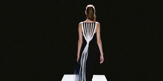 Fashion model in black and white gown walking catwalk, rear