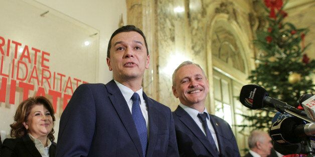 Sorin Grindeanu (C) gestures while answering a question during a press conference held alongside Romania's...