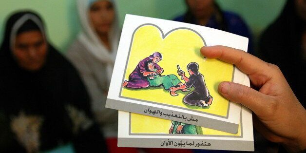 - PHOTO TAKEN 13JUN06 -A counsellor holds up cards used to educate women about female genital mutilation...