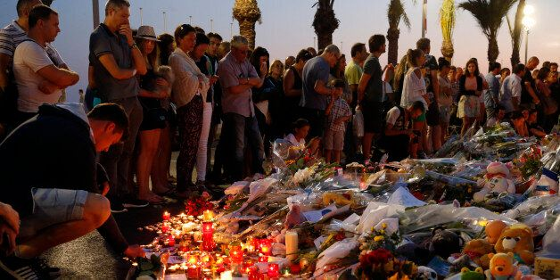 People gather around flowers and burning candles to pay tribute to victims of the truck attack along...