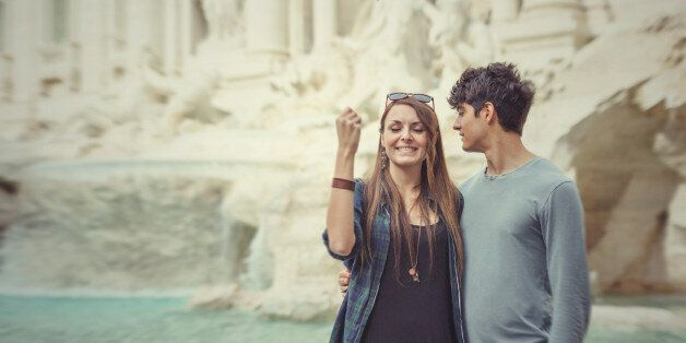 Tourist couple tossing a coin in the Trevi fountain