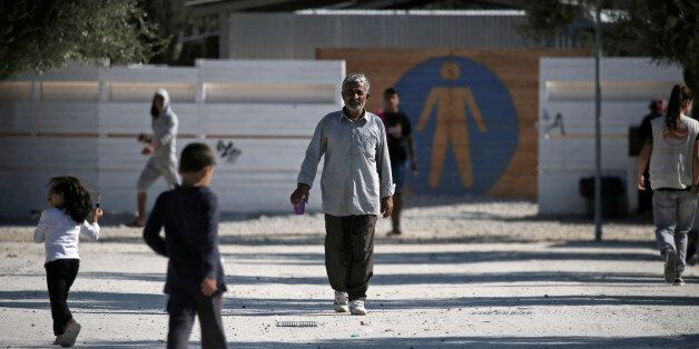 Refugees and migrants make their way at the municipality-run camp of Kara Tepe on the island of Lesbos,...