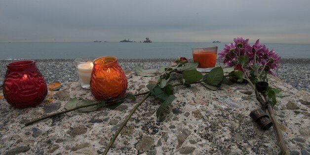 SOCHI, RUSSIA - DECEMBER 27 : Flowers and candles for the victims lay on the beach as ships are seen...