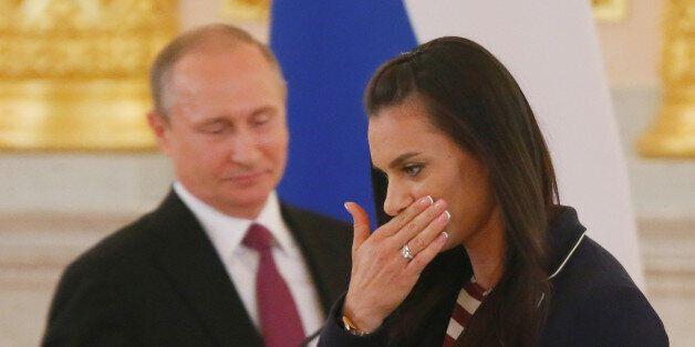 Track-and-field athlete Yelena Isinbayeva reacts as she walks past Russian President Vladimir Putin during...