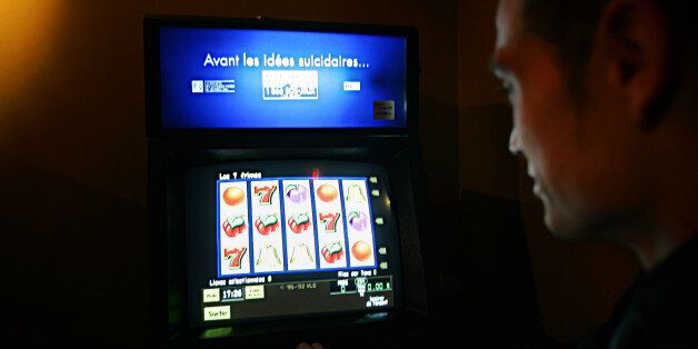A man looks at a video lottery terminal with the slogan 'Before you have suicidal thoughts.' in Montreal,...