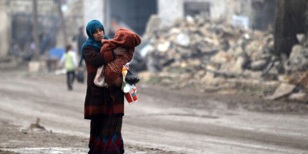 A woman carries a child as she walks near rubble of damaged buildings in al-Rai town, northern Aleppo...