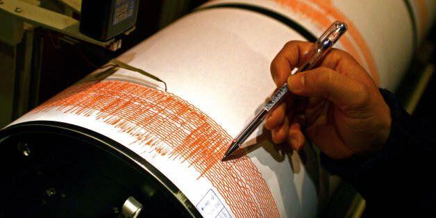 Lisbon, PORTUGAL: Portuguese seismologist Carlos Corela shows on a seismograph of the Instituto Geofisico...