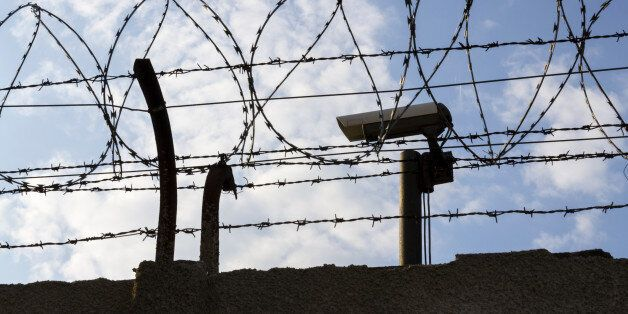 Security camera behind barbed wire fence stretched around prison