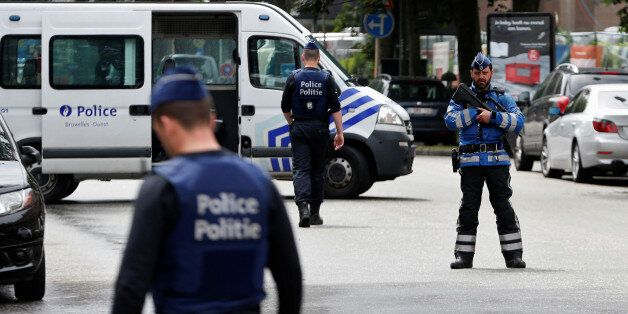 Belgian police officers stand guard near an apartment building during the reconstruction of the recent...