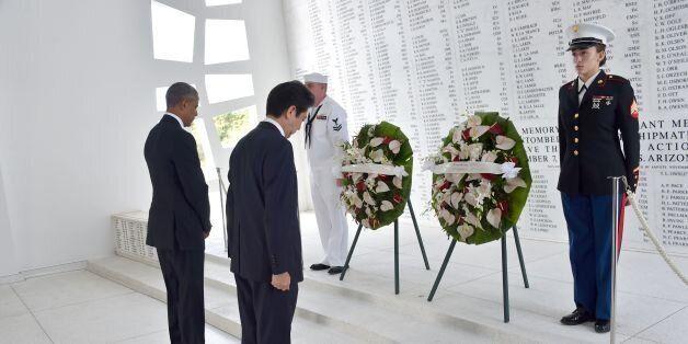 US President Barack Obama(L) and Japanese Prime Minister Shinzo Abe place wreaths at the USS Arizona...