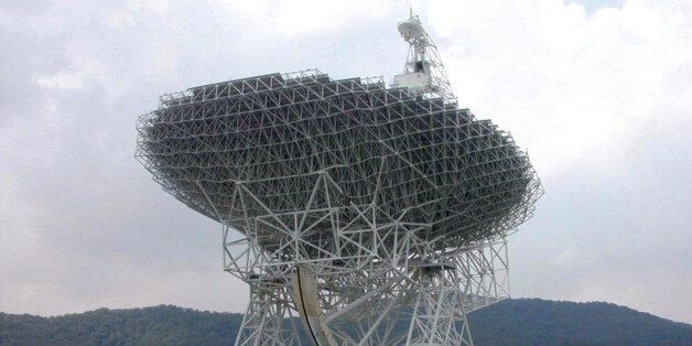 A bus parked nearby gives an idea of the size of the newest instrument at Green Bank: a radio telescope...